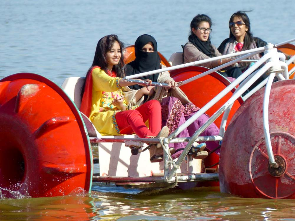 School students enjoying paddle boats on the lake.