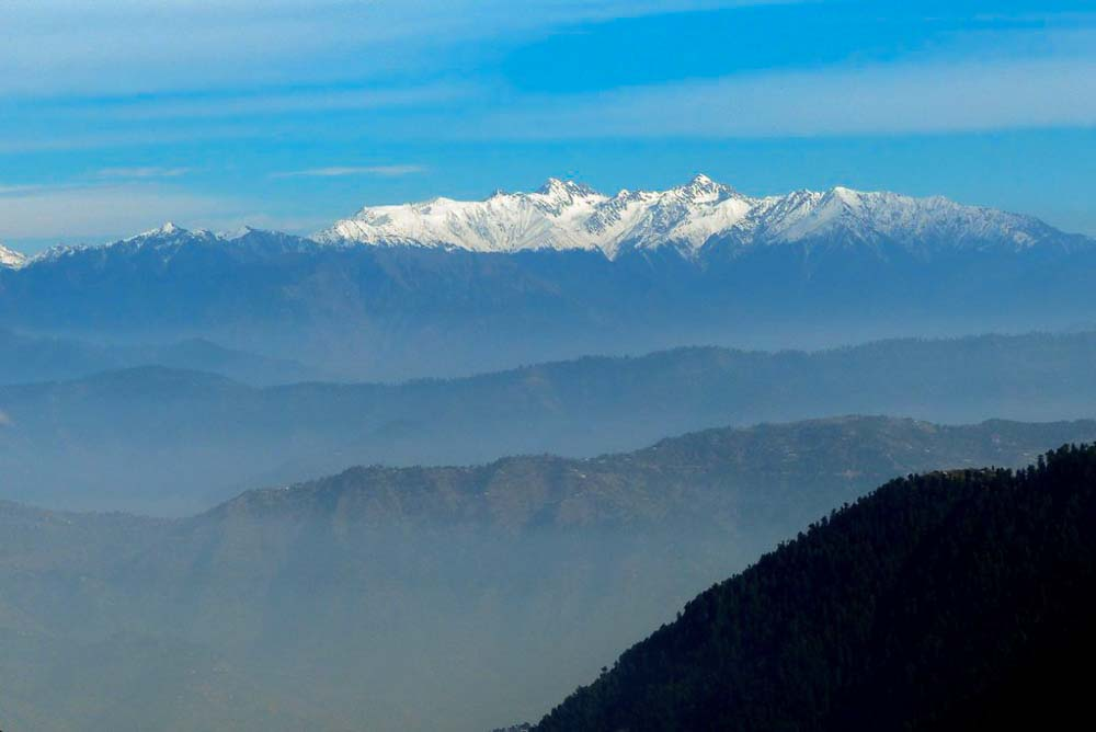 Rows of blue foothills leading up to the massive, snow capped Himalaya.