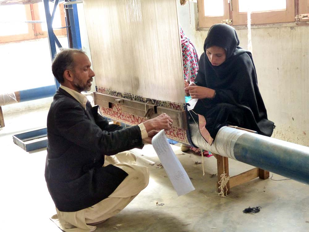 Haleem, rug instructor, working with Nadia on one of the 6 looms.