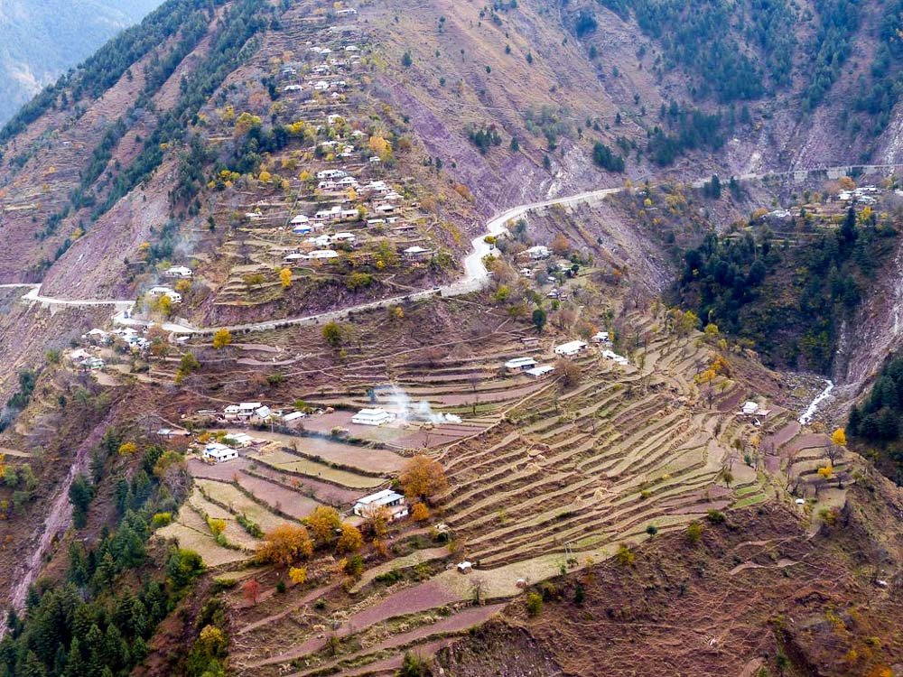 Houses cling to the steep hillsides with terraced fields nearby.