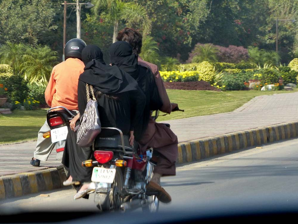 Two women riding side saddle behind the motorbike driver.