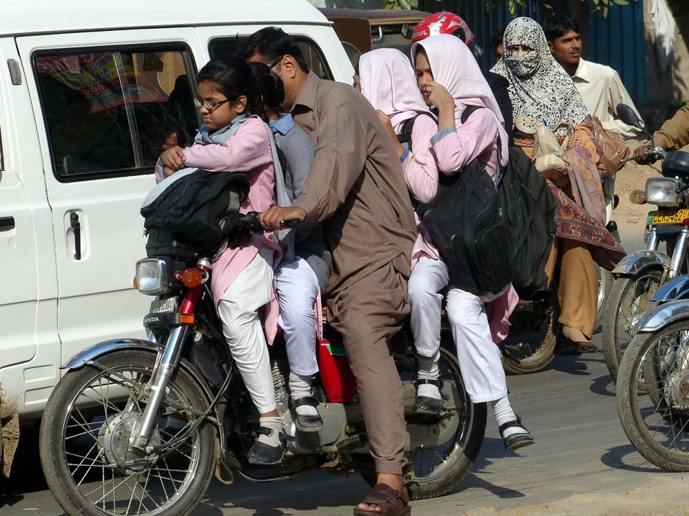School girls being picked up next door to the Bunyaad office. Dad plus 4 girls heading into rush hour traffic!