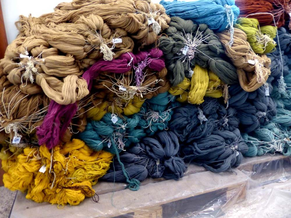 Dyed wool stacked up in the Bunyaad warehouse, ready for rug knotting.