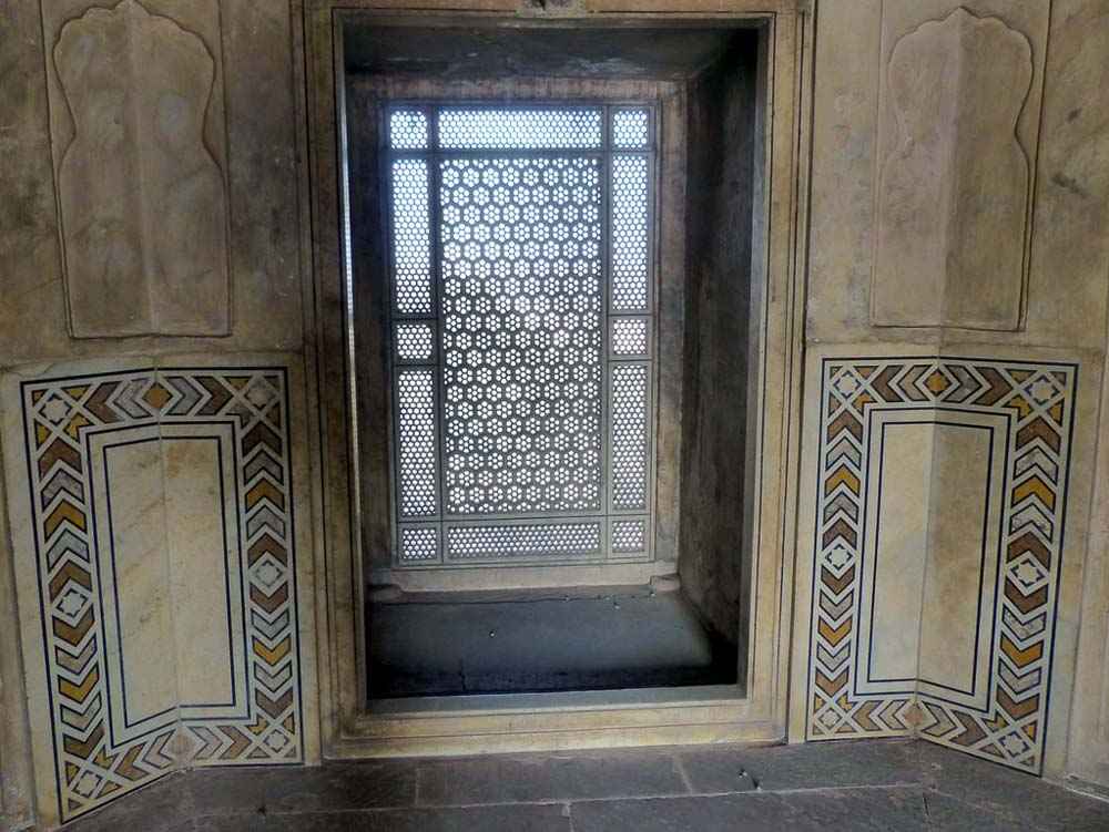Intricately carved stone grillwork window in the Sheesh Mahal.