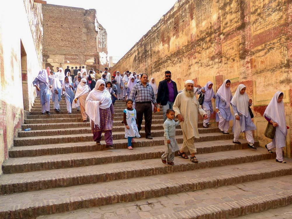 Yousaf and Afaq descending the steps on the way out of the Yousaf and Afaq walking out of Lahore Fort with crowds of friendly people on a Sunday afternoon outing.