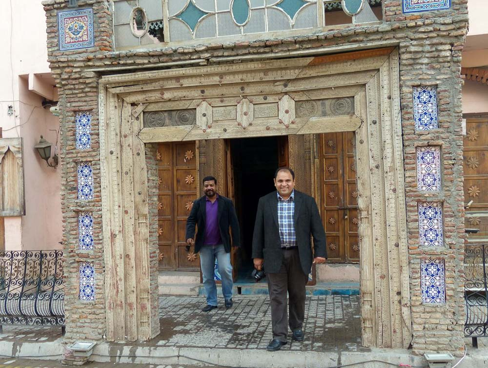 Afaq and Yousaf walking through a gateway at the entrance to a Haveli (large house or mansion from the Mughal age) just outside the old city wall.