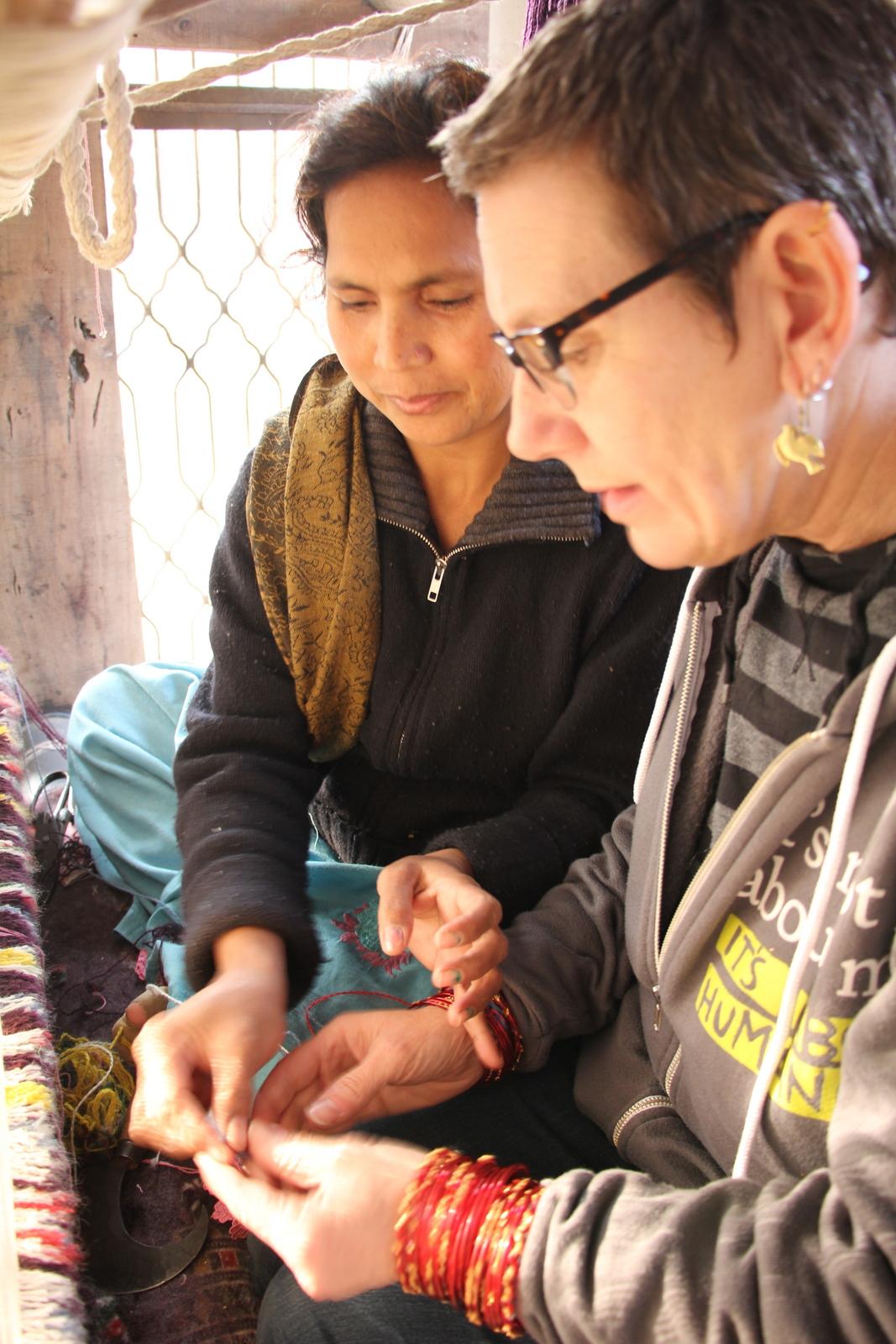 Razia teaching Gwen how to knot rugs