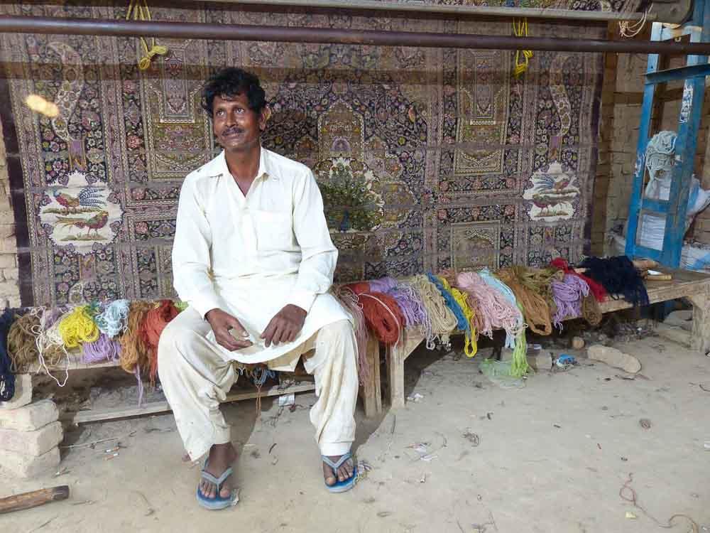 Ghulam Rasoom sitting in front of his loom.