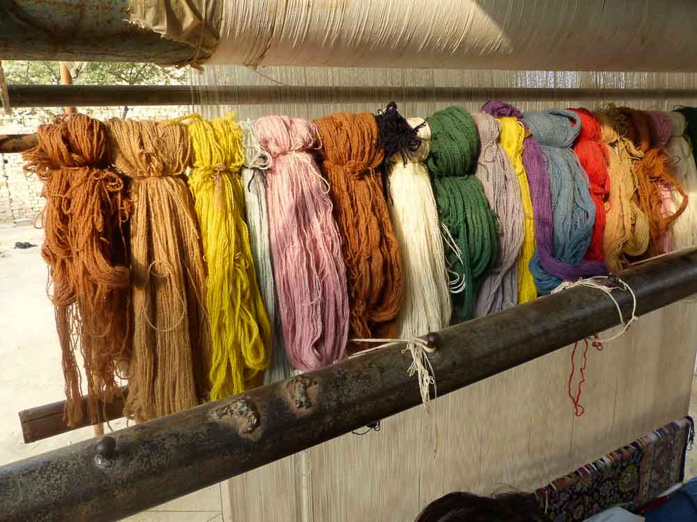 Colorful array of wool yarn above Md. Asif's loom
