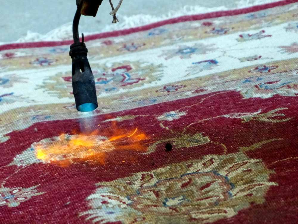 Burning the back of the carpet to get rid of extra wool fuzz.