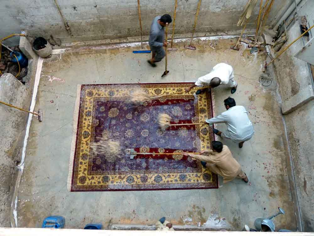 The scraping process is hard work and the water cascades out of the rug.