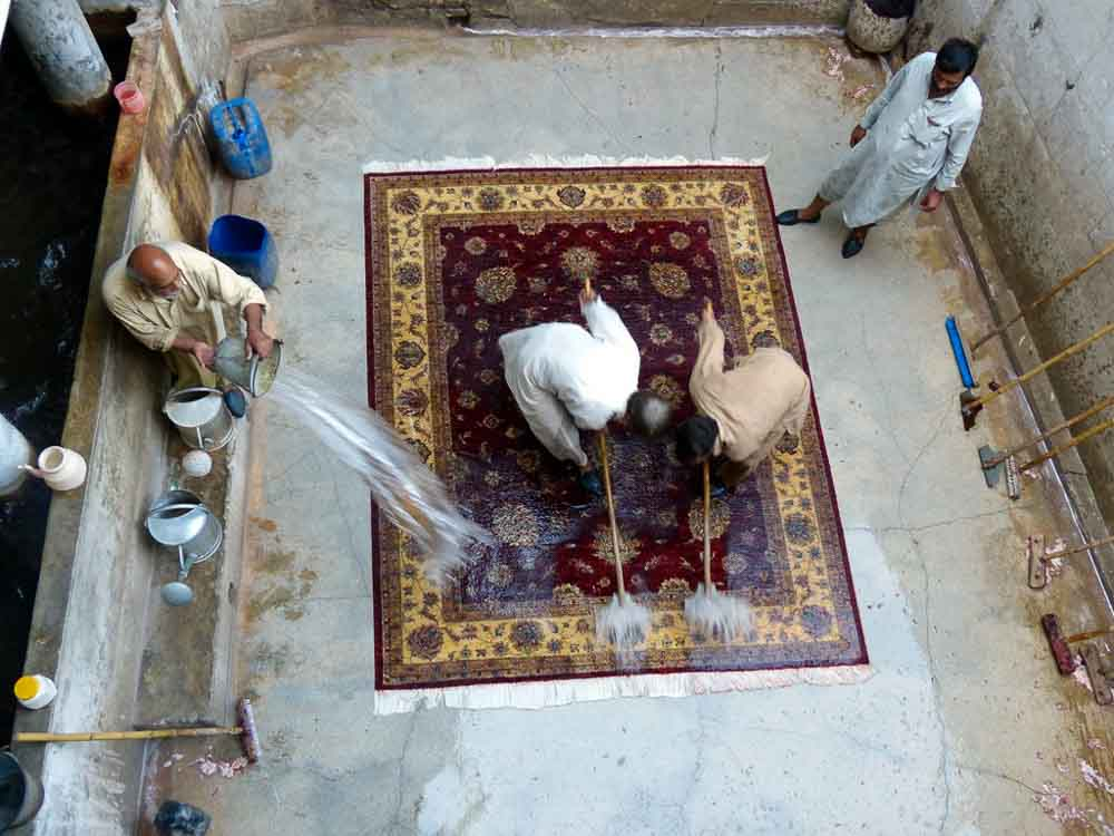 The rug is dowsed again with water and more bleach solution is added if more dirt needs to come out.