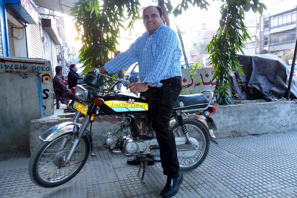 Yousaf sitting on the 'JAKCISS Company' motorcycle.