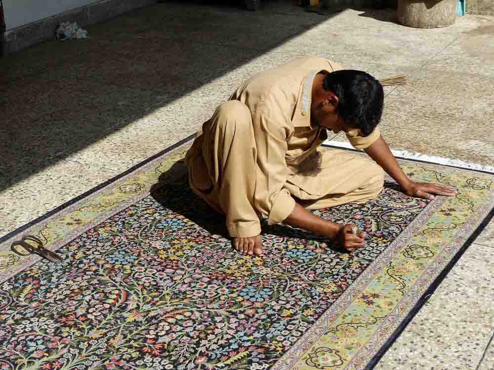 Imran working on final small details of a 4 x 6 foot tree of life Persian rug.
