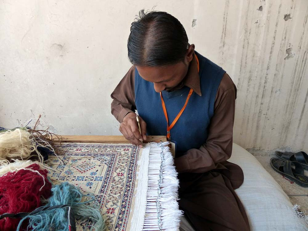 Repairing the fringe of a rug returned to Pakistan. After the repair is complete the customer will have a like-new rug.