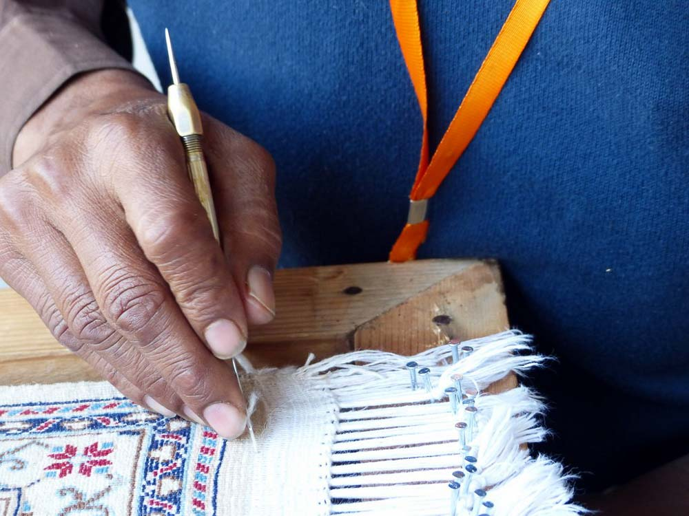 Precise and painstaking hand work is needed to repair the fringe of this rug.