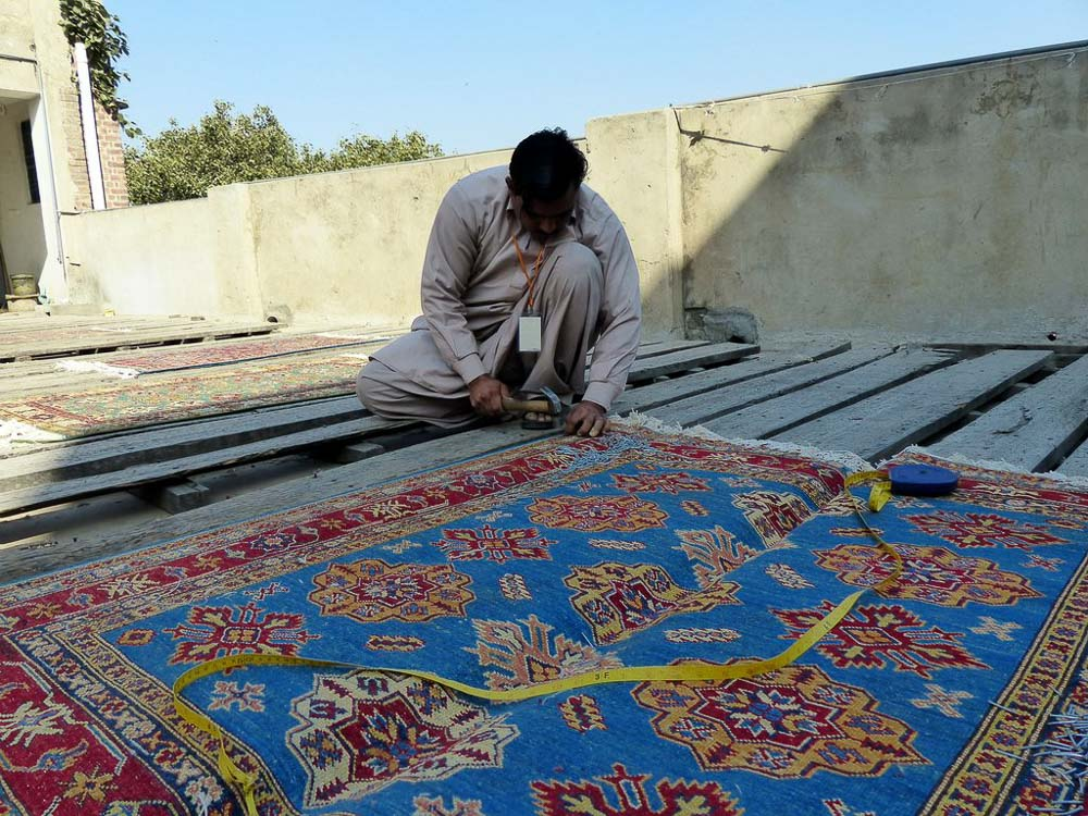 A Kazak rug is carefully measured and then nailed to the stretching platform before being stretched into the correct shape.
