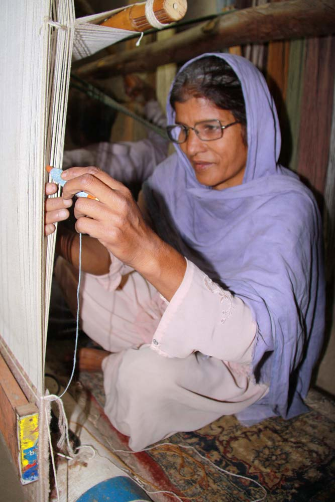 Female Bunyaad Rug Knotter adding the weft thread