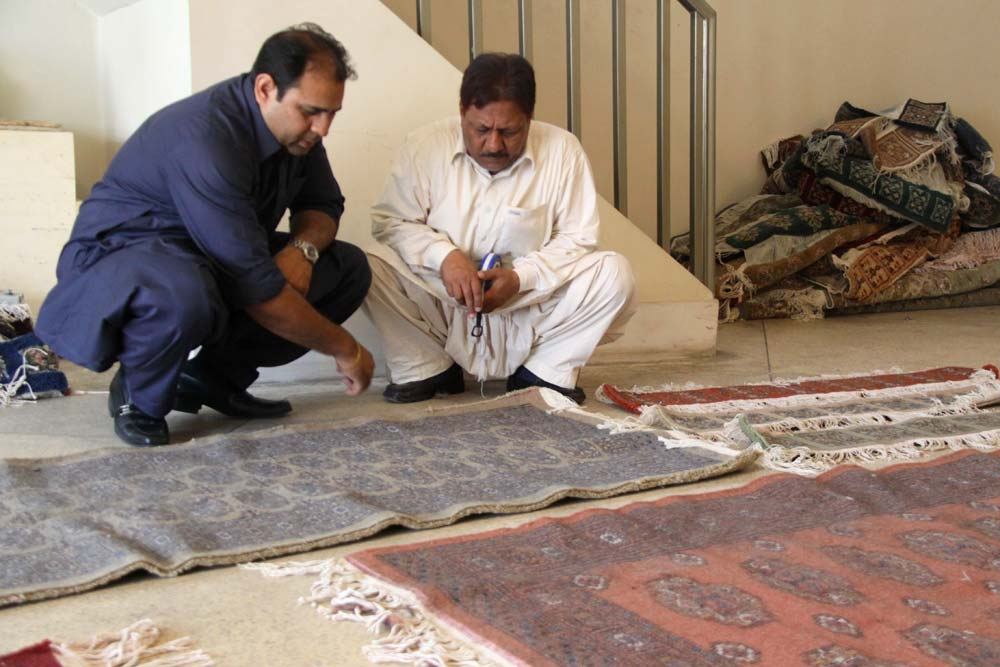 Ehsan and Ishaq are checking in rugs from the village of Sheikpura, Pakistan.