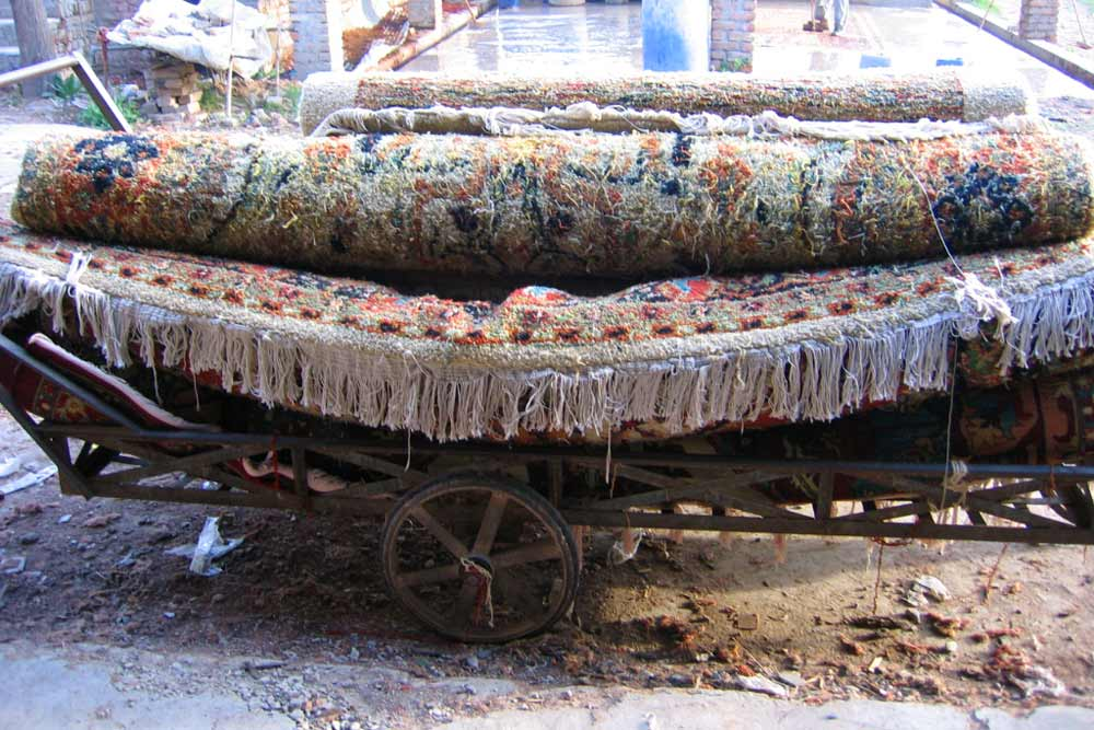 Rugs are transported on a horse-drawn cart known as a tonga. Lahore, Pakistan