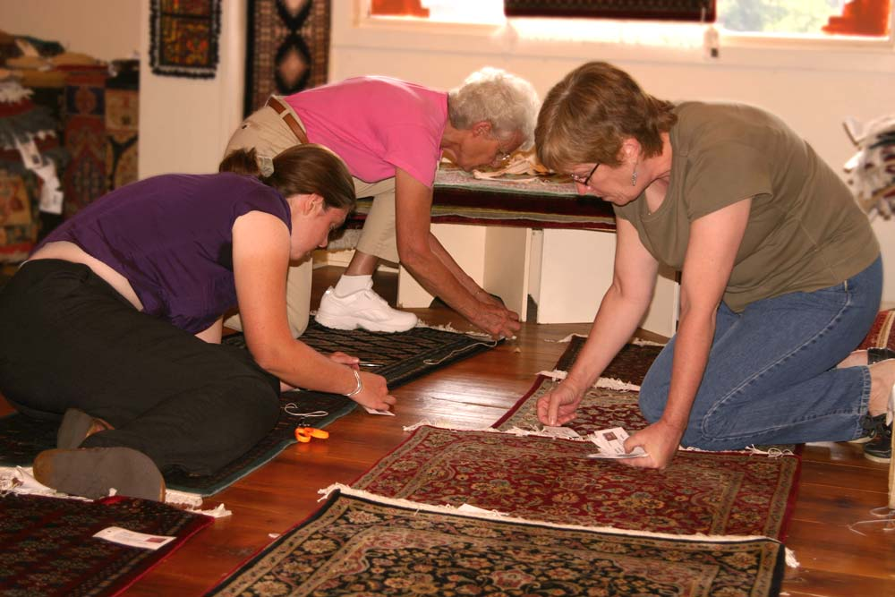 Staff and volunteers check in new Bunyaad rug shipment